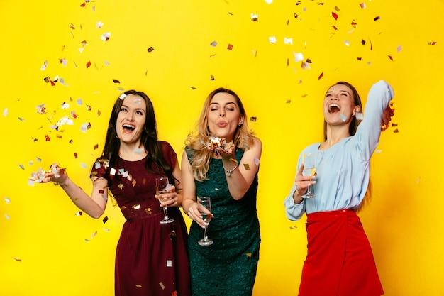 Feliz 8 de março. alegres garotas bonitas brincando com confete, soprando, se divertindo juntos
