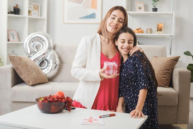 Feliz, abraçada, a filha dá um presente para a mãe no feliz dia da mulher na sala de estar