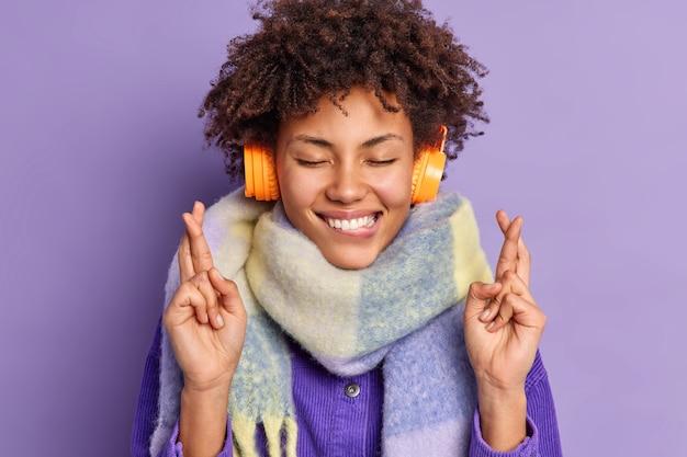 Feliz adolescente afro-americana mantém os olhos fechados mordidas lábios levantados cruzes supersticiosas dedos para dar sorte usa fones de ouvido no lenço ao redor do pescoço