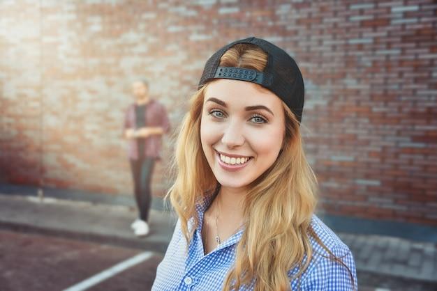 Feliz adolescente caucasiana usa boné e camisa pretos, vai passear com os amigos e posa contra a superfície branca. mulher jovem vestida com roupas da moda.