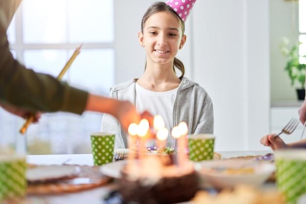 Feliz adolescente latina na tampa do aniversário, sorrindo e olhando para o bolo de aniversário, enquanto comemorava o aniversário com a família em casa. crianças, conceito de celebração