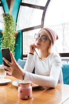 Feliz adorável jovem de chapéu e óculos, comendo e fazendo selfie com smartphone no café