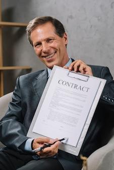 Feliz advogado maduro, apontando para o lugar de assinatura em um documento de contrato com caneta
