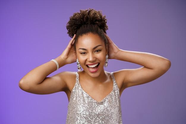 Feliz afortunada mulher encantadora afro-americana comemorando terminar a universidade curtindo a festa se divertindo dançando tocando cabelo otimista sorrindo amplamente desfrutar de fundo azul rico estilo de vida.