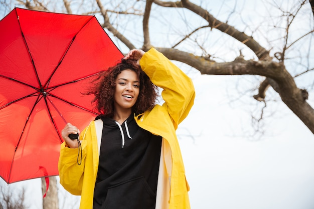 Feliz africana encaracolada jovem vestindo casaco amarelo com guarda-chuva.