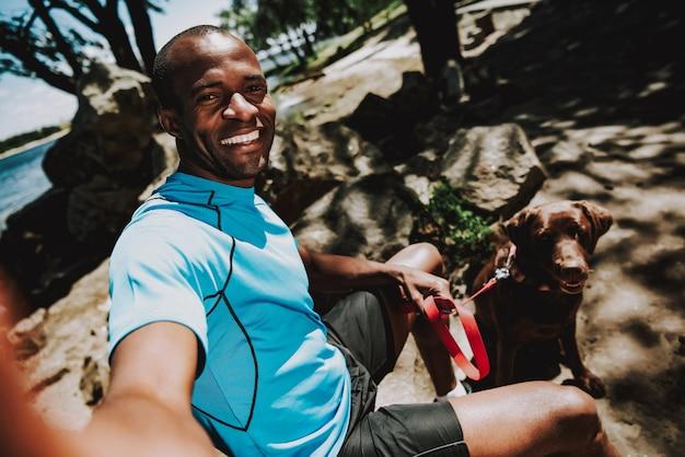 Feliz, africano, homem, com, cão, fazendo, selfie