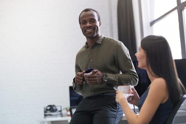 Feliz afro americano cara conversando com uma colega