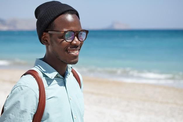 Feliz afro-americano jovem atraente vestido com roupas da moda e acessórios relaxantes à beira-mar, contemplando a paisagem azul no clima ensolarado e calmo, sentindo a conexão e harmonia com a natureza