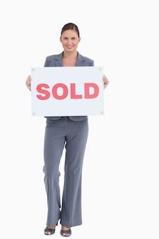 Feliz agente imobiliário segurando sinal vendido