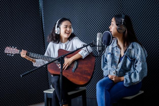 Feliz, alegre, bonito, sorrindo, retrato dois jovens asiáticos vocalista usando fones de ouvido com uma guitarra gravando uma música na frente do microfone em um estúdio profissional