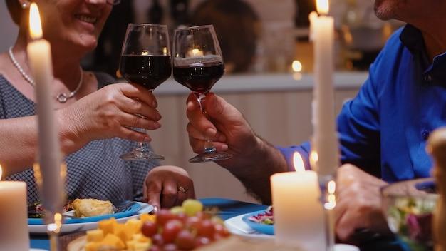 Feliz alegre casal de idosos sênior jantando junto com vinho tinto na cozinha aconchegante. idosos aposentados apreciando a refeição, comemorando seu aniversário na sala de jantar.