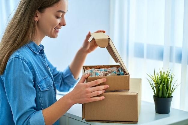 Feliz, alegre, casual, jovem, atraente, sorridente, mulher, recebeu um pacote de uma loja na internet