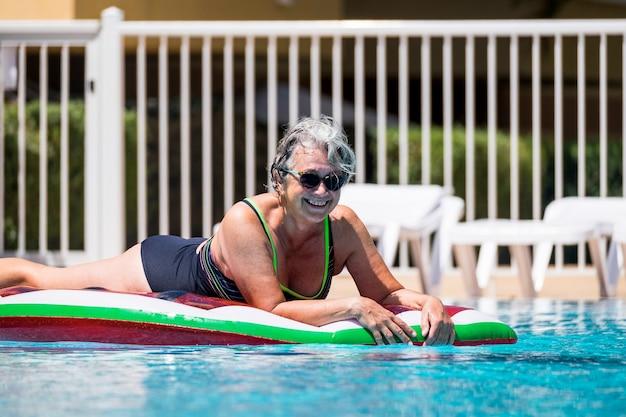 Feliz, alegre, caucasiana, idosa, velha, deitada em, colorido, moderno, lilo, aproveitando, natação, piscina, atividades de lazer ao ar livre, no verão, para, férias ou, relaxar, cidade
