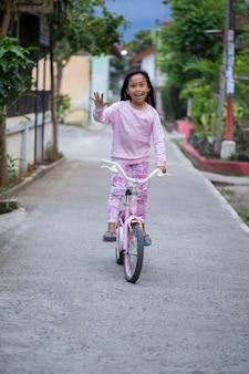 Feliz alegre criança asiática andando de bicicleta