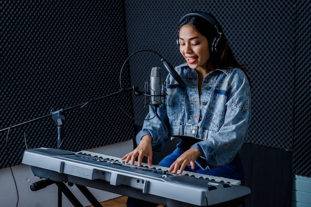 Feliz, alegre e sorridente de jovem vocalista asiática usando fones de ouvido, gravando uma música na frente do microfone e tocando o teclado durante o ensaio de sua banda em um estúdio profissional