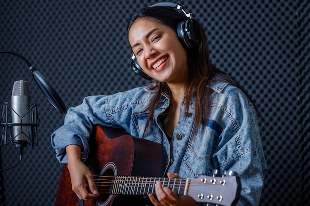 Feliz, alegre e sorridente do retrato de uma jovem vocalista asiática usando fones de ouvido com uma guitarra gravando uma música na frente do microfone em um estúdio profissional