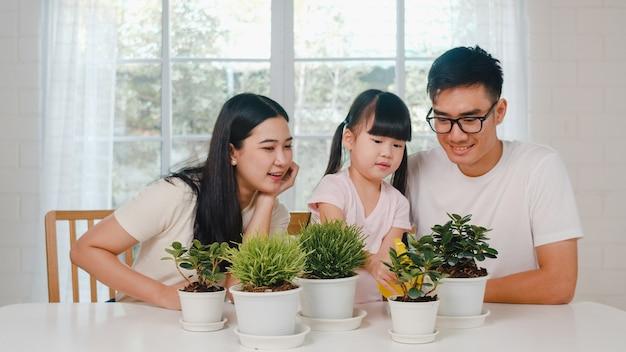 Feliz alegre família asiática pai, mãe e filha regando plantas em jardinagem perto de janela em casa