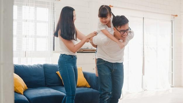 Feliz alegre família asiática pai, mãe e filha se divertindo jogando