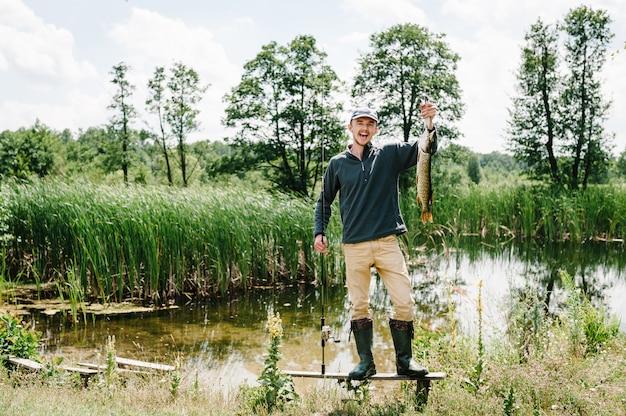 Feliz alegre jovem pescador segurar um peixe grande pique em um fundo de lago e natureza