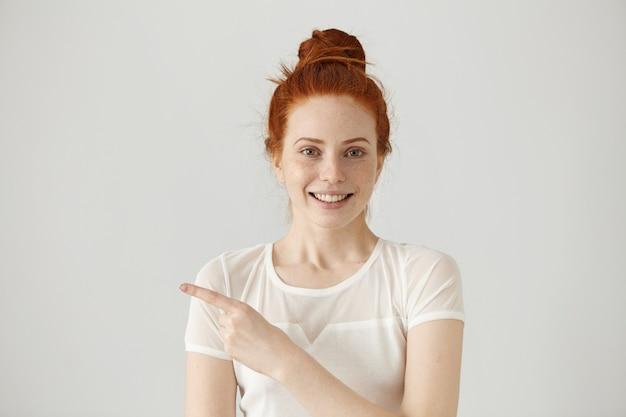 Feliz alegre jovem ruiva caucasiana com coque de cabelo apontando o dedo indicador para longe