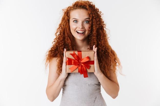 Feliz alegre jovem ruiva encaracolado segurando o presente da caixa surpresa.