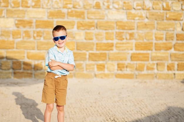 Feliz alegre lindo garotinho contra a parede de tijolos amarelos.
