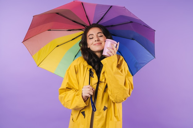 Feliz alegre mulher morena em capa de chuva amarela posando isolado sobre a parede roxa segurando guarda-chuva e café.