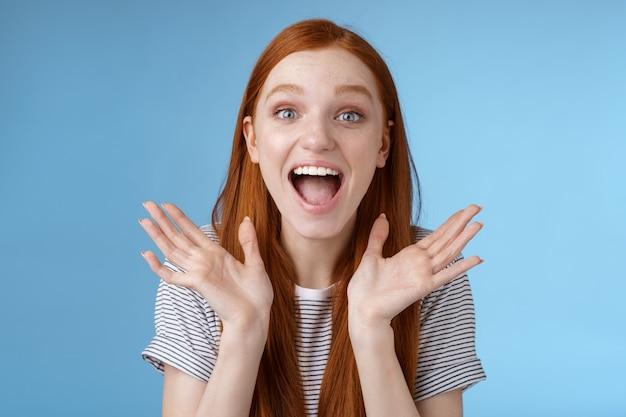 Feliz alegre regozijando jovem ruiva bonita namorada apoiadora apertar as mãos alegremente gritando parabéns, levantando as mãos divertidas olhos arregalados surpreso por receber uma boa notícia incrível, fundo azul.