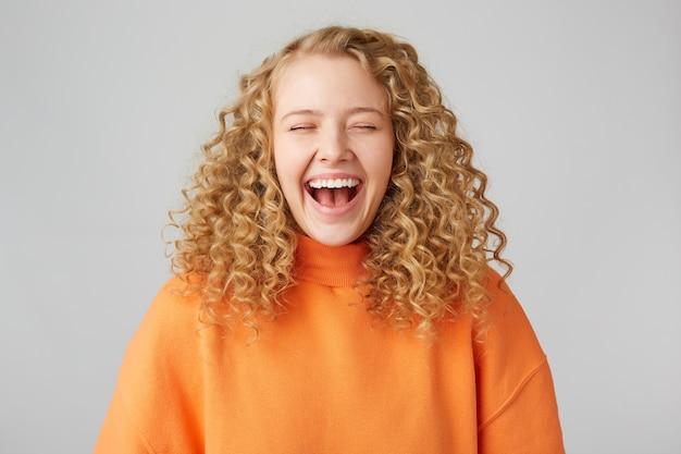 Feliz, alegre, resiliente, loira de cabelos cacheados fechou os olhos de prazer, aproveita o momento rindo, vestindo um suéter laranja quente grande demais