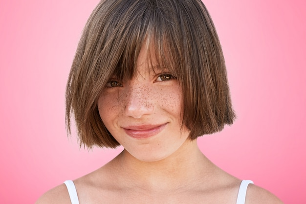 Feliz alegre sorridente criança alegre com penteado cortado olha alegremente para a câmera, se alegra passar o tempo livre com os pais que compraram seu novo brinquedo. poses de menina muito adorável no estúdio