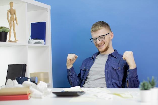 Feliz alegria homem caucasiano em camisa casual mantém as mãos levantadas