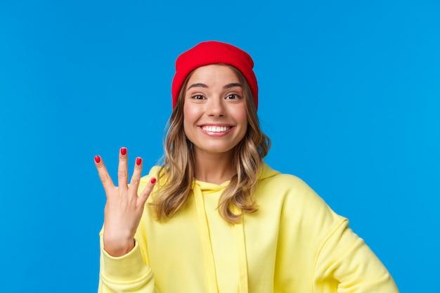 Feliz aluna sorridente no gorro hipster vermelho, mostrando o número quatro, quarto e sorrindo otimista, fazer reserva ou ordem, em pé parede azul otimista