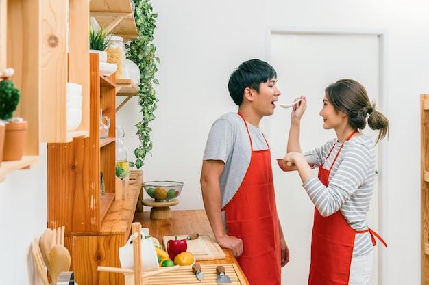 Feliz amante asiática ou casal cozinhar em ação de felicidade na sala de cozinha