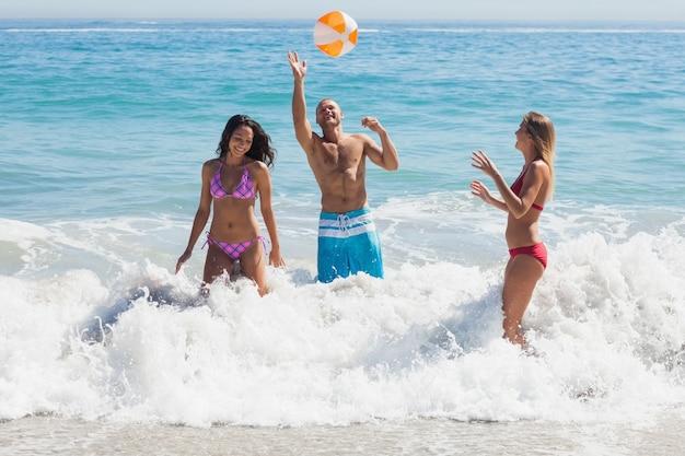 Feliz amigos brincando com uma bola de praia no mar