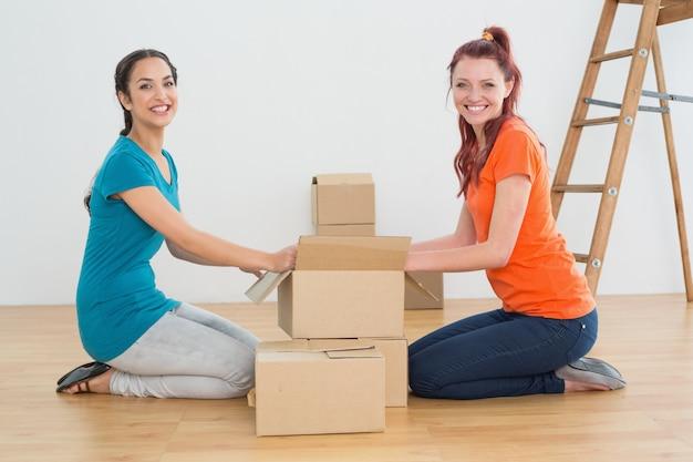 Feliz amigos desempacotando caixas em uma nova casa