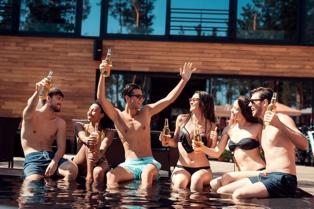 Feliz amigos enoying festa na piscina com alcoólatra.