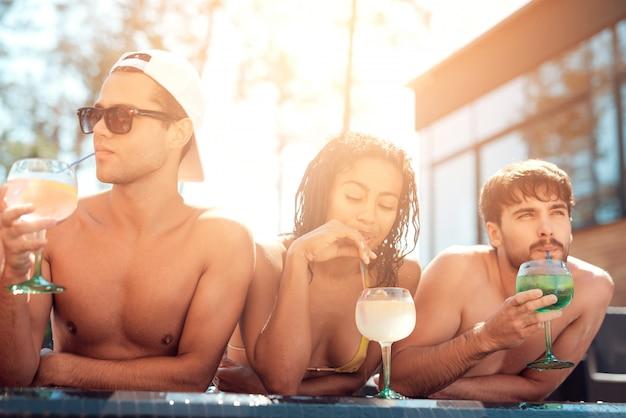 Feliz amigos enoying festa na piscina. conceito de férias de verão