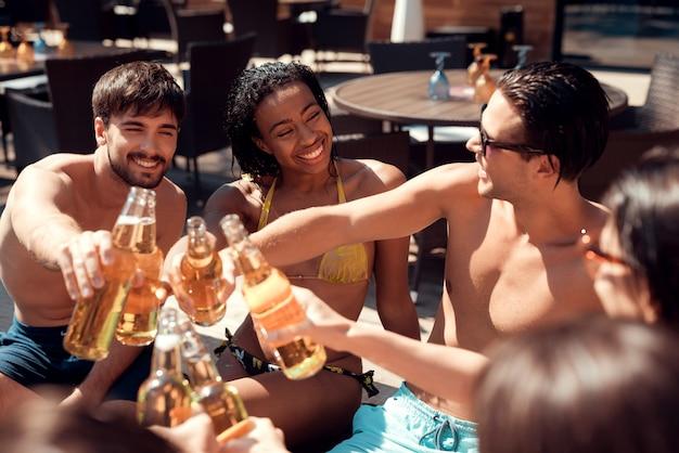 Feliz amigos enoying festa na piscina.