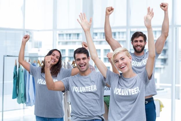 Feliz amigos voluntários, levantando os braços