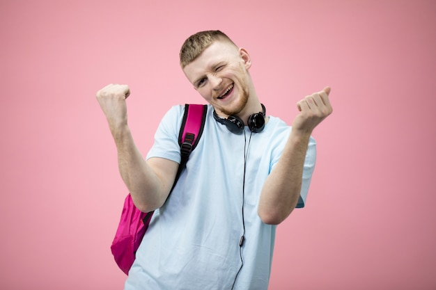 Feliz animado alegre alegre estudante comemora sua vitória com as mãos levantadas.