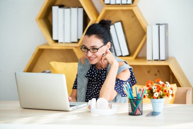 Feliz animado bem sucedida empresária bonita triunfando no escritório moderno com laptop, pose feliz de sucesso