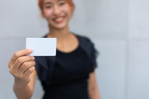 Feliz animado e bem-sucedida bela empresária segurando o cartão de crédito simulado por lado.