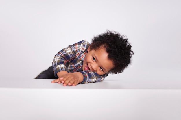 Feliz animado garotinho afro-americano em roupas casuais posando isolado no branco