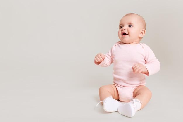 Feliz animado infantil bebê menina criança vestindo bodysuit e meias sentado no chão, isolado na parede branca, olhando para longe com a boca aberta no espaço da cópia gratuita.