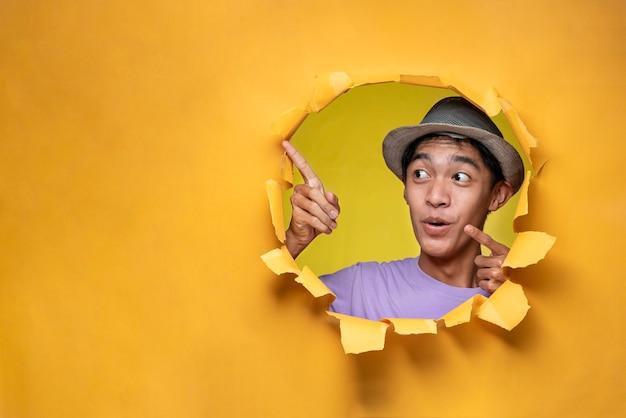 Feliz animado jovem adolescente asiático posa através do buraco de papel amarelo rasgado, apontando um espaço de cópia, vestindo camiseta roxa e chapéu, anunciando o melhor produto. negócios de publicidade.