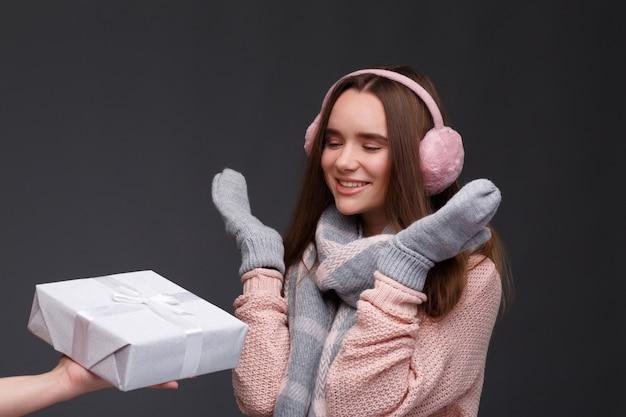 Feliz animado jovem sorridente garota feliz no pulôver de tricô e protetores de orelha macios rosa com caixas de presente.