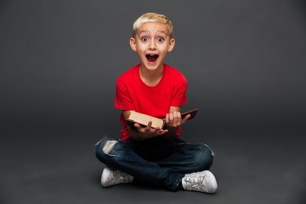 Feliz animado menino criança lendo livro.