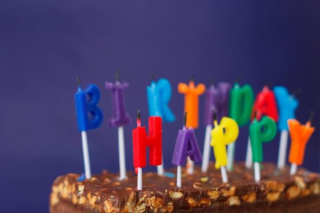 Feliz aniversário brownie cake com amendoins, caramelo salgado e velas não iluminadas coloridas na superfície violeta. copie o espaço para texto.