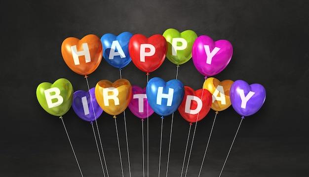 Feliz aniversário colorido com balões de ar em forma de coração em uma cena de superfície preta