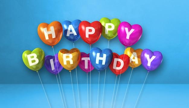 Feliz aniversário colorido em forma de coração balões de ar em uma cena de superfície azul